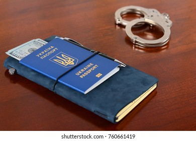 In Ukraine, corruption must be punished by law and not be a home for corrupt people. Ukrainian biometric passport and handcuffs on the table.