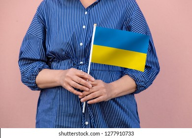 Ukraine flag. Close up of woman's hands holding  a national flag of Ukraine.