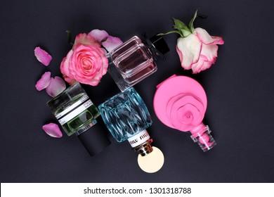 Ukraine - January 15, 2019: Perfumes set on black background with flowers: MIU MIU, Green Water, Giorgio Armani, Valentino, Gucci