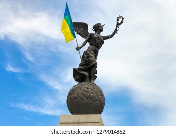 UKRAINE, KHARKIV - JULY 28, 2018 : Constitution Square. Flying Ukraine - Independence monument ( Kharkiv sculptor Alexander Ridny). Ukrainian national state flag fluttering