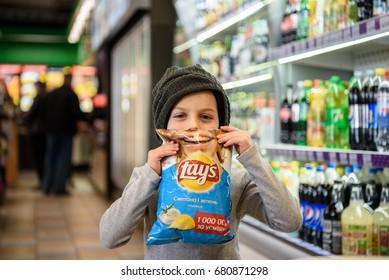 Ukraine, Kharkov - April 08, 2017: The little boy chooses chips at the WOG gas station, Kharkov region