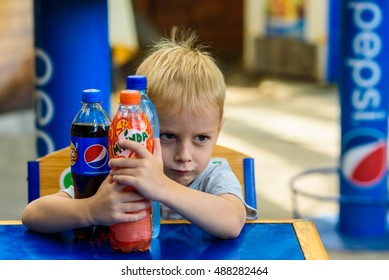 Ukraine, Kharkov - September 11, 2016: Little boy holds bottles of Pepsi, Mirinda in Kharkov Ecopark