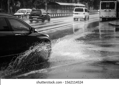 Ukraine. Kiev - 05,12,2019 Spraying water from the wheels of a vehicle moving on a wet city asphalt road. The wet wheel of a car moves at a speed along a puddle on a flooded city road during rain