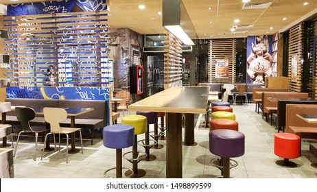 Ukraine, Kiev - August 19, 2019: McDonald's restaurant interior. McDonald's is the world's largest fast food restaurant chain based in the USA. Interior with tall tables and colored bar stools