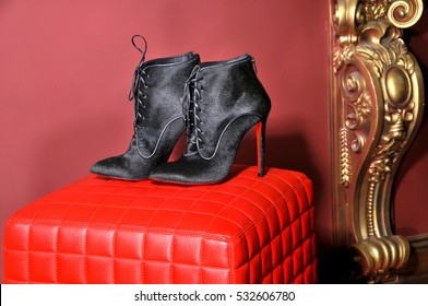 Ukraine, Kiev - August 25, 2016:  Women's ankle boots handmade. Imitation brand shoes Christian Louboutin, showing red soles   - illustrative editorial.