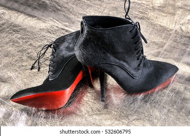 Ukraine, Kiev - August 25, 2016: Women's boots handmade on a piece of material from the golden skin. Imitation brand shoes Christian Louboutin, showing red soles illustrative editorial