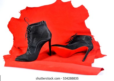 Ukraine, Kiev - August 25, 2016: Women's black ankle boots handmade on a piece of material from the red skin. Imitation brand shoes Christian Louboutin, showing red soles - illustrative editorial