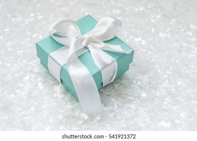 Ukraine, Kiev - December 23, 2016: Tiffany box tied with silk ribbon, surrounded by artificial snow on a white background closeup