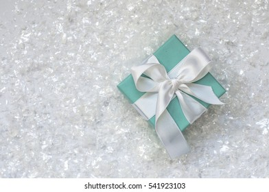Ukraine, Kiev - December 23, 2016: Tiffany box tied with silk ribbon, surrounded by artificial snow on a white background, top view