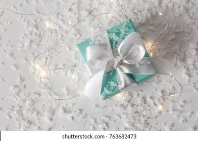 Ukraine, Kiev - November 27, 2017: Branded Tiffany box with silk ribbon surrounded by small lights and artificial snow on a white background top view