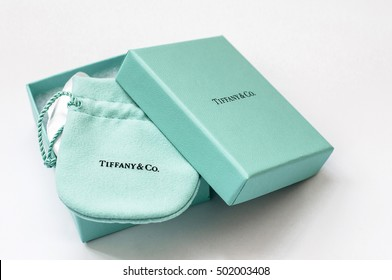 Ukraine, Kiev - October 19, 2016: Open Tiffany branded box with a gift inside, packed into a cloth bag, on a white background