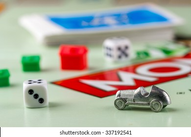 Ukraine, Kiev - October 29, 2015: Close-up view of Monopoly game pieces: car, pair of dice, houses, cards on board. Focus on the toy car