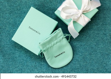 Ukraine, Kiev - September 30, 2016: Two brand Tiffany box with silk ribbon and velvet pouch on knit cloth cover of turquoise color