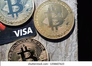 Ukraine, Kremenchug - March, 2019: Golden Bitcoins on Visa card and wooden background