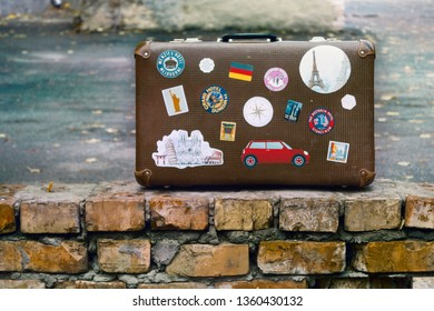 UKRAINE, KYIV, 1 JANUARY 2019: old suitcase covered with travel stickers standing on brick wall, ready for new trip
