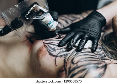 UKRAINE, KYIV - JANUARY 8, 2019;  Kiev tattooist Vlad Zrub in the process of creating a new tattoo on chest