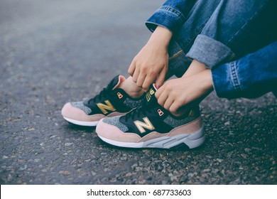 UKRAINE, KYIV - JULY 28, 2017:Young handsome girl wearing a fashionable outfit in the city. Female feet in jeans and sports shoes. Woman with pink and black New Balance shoes