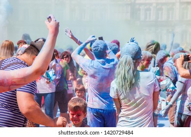 """Ukraine, Kyiv - June 2, 2019:  """"Kyiv Color Run"""" - fun run with spraying Holi colors. Running fun people with soiled faces and clothes. Multicolored powder on the crowd of people who jogging."""