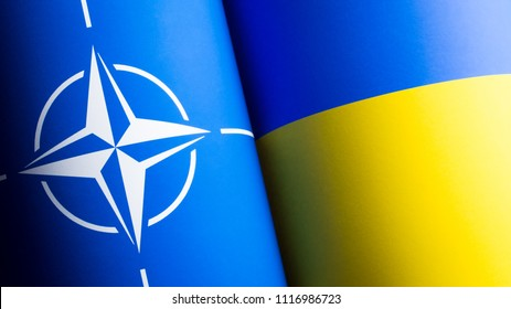 Ukraine, Kyiv - June 6, 2018: Flags of NATO and Ukraine printed out on the paper waving together. Partnership of Ukraine and North Atlantic Treaty Organization