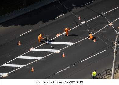 UKRAINE, KYIV - May 25, 2020: Road workers painting marking white line on the road surface. Thermoplastic spray marking machine during road construction.