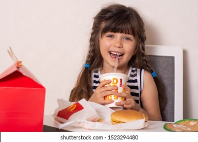 Ukraine, Kyiv - ocotber 5, 2019: smiling girl holding drinking soft drink soda sold as part of the McDonald's Happy meals, from McDonald's restaurant