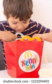 Ukraine, Kyiv - ocotber 5, 2019: smiling boy holding happy meal box from McDonald's restaurant