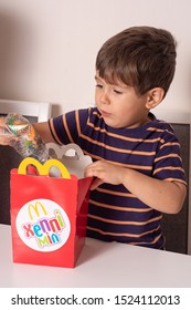 Ukraine, Kyiv - ocotber 5, 2019: smiling boy holding happy meal box from Mc Donald's restaurant