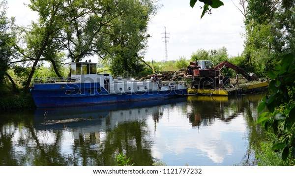 Ukraine, Lutsk 27.06.18 clearing of the river bed of Styr, a boat, a barge, an ekskovator.
