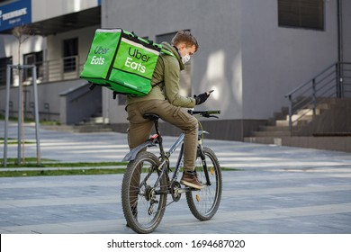Ukraine. Lviv. 03/05/2020. Editorial. Food supplier with Uber Eats backpack riding a bike on the street. A masked courier delivers food in a pandemic.
