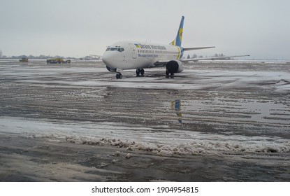 Ukraine, Lviv - March 1, 2009: Winter at the airport. A passenger plane stands on a snow-covered platform. Snow removal equipment is working on the runway. UIA plane Boeing 737-341  UR-GAL. Snow