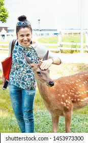 Ukraine, Mezhygirya, May, 2019. A girl in a summer park stroked on the head of a young bambi