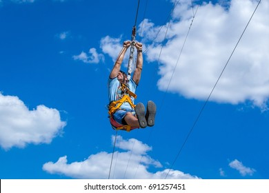 Ukraine, Migea - July 30, 2017: Zipline. A view of a man sliding on a steel cable against a beautiful blue sky with white clouds. Extreme and active rest.