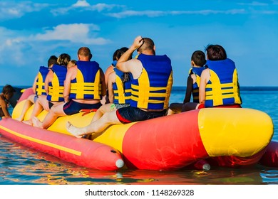 Ukraine, Odessa, July 2018:man is riding an inflatable water attraction. group of people in marine lifejacket sits on the Water Inflatable Boat Ride