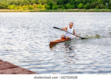 Ukraine, Odessa, summer 2019. Rear view of a kayaker man paddle a canoe on a canal. Kayaking, canoeing, rowing. Water sport.