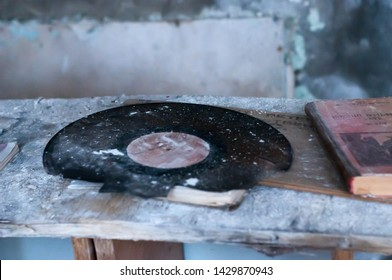 Ukraine, Pripyat, Chernobyl zone of alienation - 31.03.2018: soviet textbook and black vinyl record on table in ruined school on table in destroyed school in Pripyt, Chernobyl zone of alien