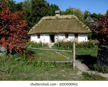 Ukraine, Pyrohiv (Kiev) - September 17, 2017: A typical Ukrainian traditional national rural landscape is a house with white walls under a thatched roof and in the courtyard a flower garden