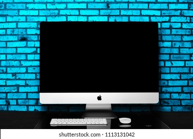 UKRAINE, RIVNE, June 15, 2018. Apple Computer iMac 27 retina display 5K keyboard and magic mouse on black table. Isolated on a blue background