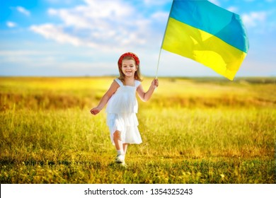 Ukraine s blue-yellow flag flying in wind in hands of little Ukrainian girl on Day of ndependence of Ukraine. Symbols of Ukraine in hands of a smiling child against blue sky and yellow grass.