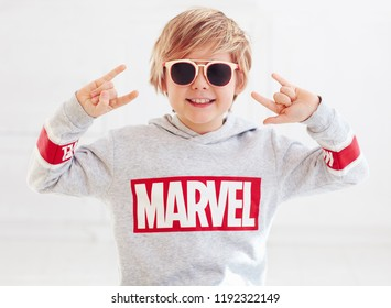 Ukraine- September 30, 2018: Portrait of blonde smiling boy with rock finger sign and marvel logo on sweater