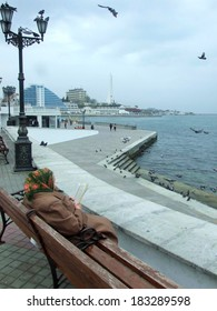 UKRAINE, SEVASTOPOL � CIRCA MAY 2010: Unknown grandmother reads a political newspaper at sea embankment circa May 2010 in Sevastopol, Ukraine.