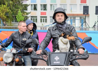 UKRAINE, SHOSTKA - May 4, 2019: Biker with kind eyes sits with his dog on his motorcycle.