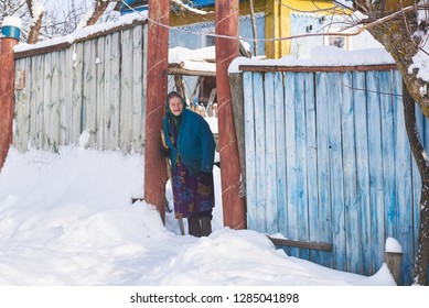Ukraine, Svirzh, St. Lesnaya - January 13, 2019: Old grandmother with a stick stands near her house in the village in winter