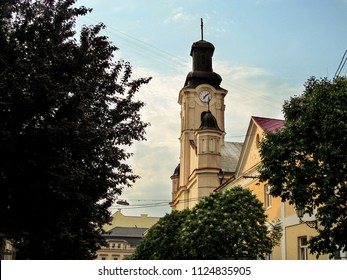 Ukraine, Uzhhorod - April 30, 2018: The Church of St. George in Uzhgorod. An ancient church tower with a round clock in a mixed Baroque and Neo-Baroque style against a blue sky
