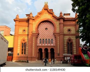 Ukraine, Uzhhorod - April 30, 2018: Uzhgorod Synagogue building or Regional Philharmonic Hall, close-up. Beautiful old red brick building with a mosaic facade