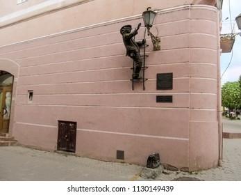 Ukraine, Uzhhorod - April 30, 2018: Sculpture Uncle Kolya-lamplighter on the wall in Uzhgorod. A bronze man on the stairs lights a lantern, the sculptor Mykhailo Kolodko