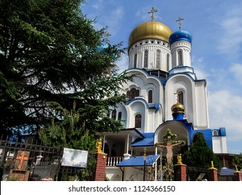 Ukraine, Uzhhorod - April 30,2018: An amazing orthodox Cyril and Methodius Cathedral in sunny summer day. Green spruce, blue sky, majestic temple with golden and blue domes and holy crucifix, close-up