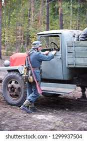 Ukraine, Voronezh - September 2, 2018: Reconstruction of the Second World War, german soldier stands near the car in the forest.