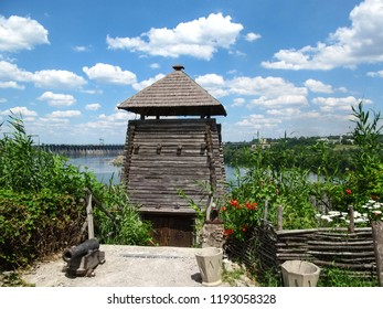 Ukraine, Zaporizhia - June 27, 2016: Defensive wooden construction of Cossacks in the complex 'Zaporozhye Sich'. A bright view on the  Dneprostroi Dam from Cossack camp on the island of Khortytsia