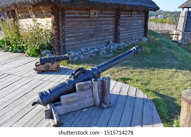 Ukraine, Zaporizhia - October 6, 2018: Old wooden hut, wooden fence, Smoothbore guns - firearms on wooden flooring in the old Zaporozhye fortress. Guns guard the approaches to the old fortress.