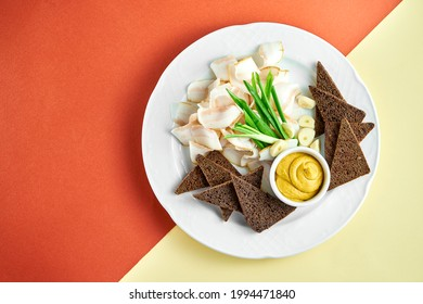 Ukrainian appetizer sliced bacon (salo) with rye bread and mustard on a white plate on bright colored backgrounds